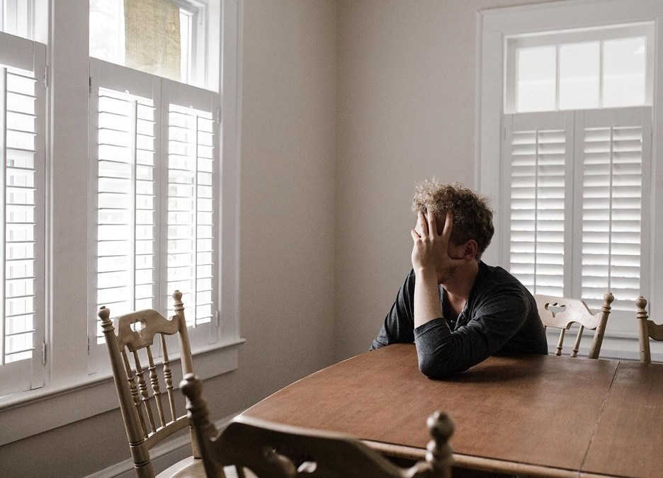 A man sits at a dining table with his head in his hands in a bright room. This image represents the mental health struggles of those that suffer from trauma and PTSD.
