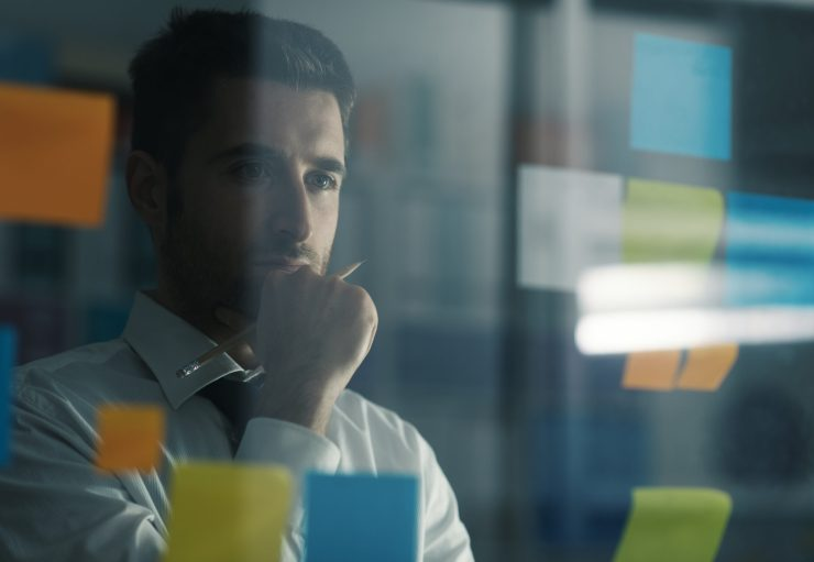 Business executive reading sticky notes on a glass, he is thinking about creative business solutions and strategies