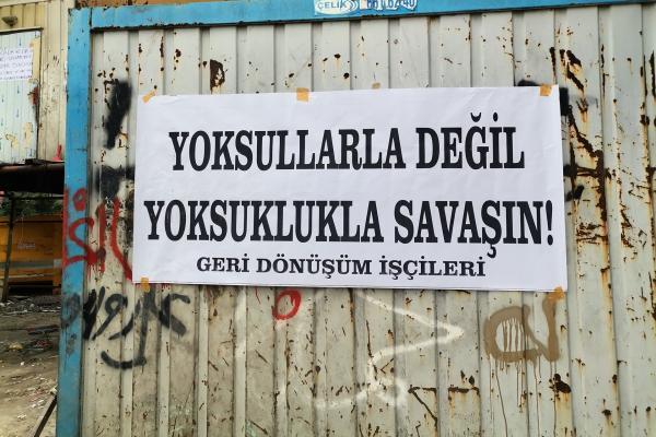 Geri dönüşüm işçilerinin basın açıklaması esnasında bir konteynere yapıştırılmış olan 'Yoksullarla değil yoksullukla savaşın' yazılı pankart.