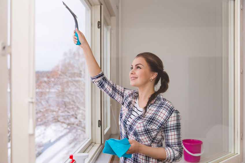 49922956 – smiling young woman cleaning windows in winter