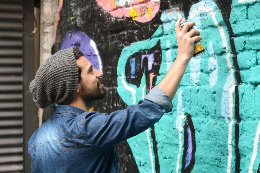46044444 – young urban latin painter drawing a graffiti on the wall.