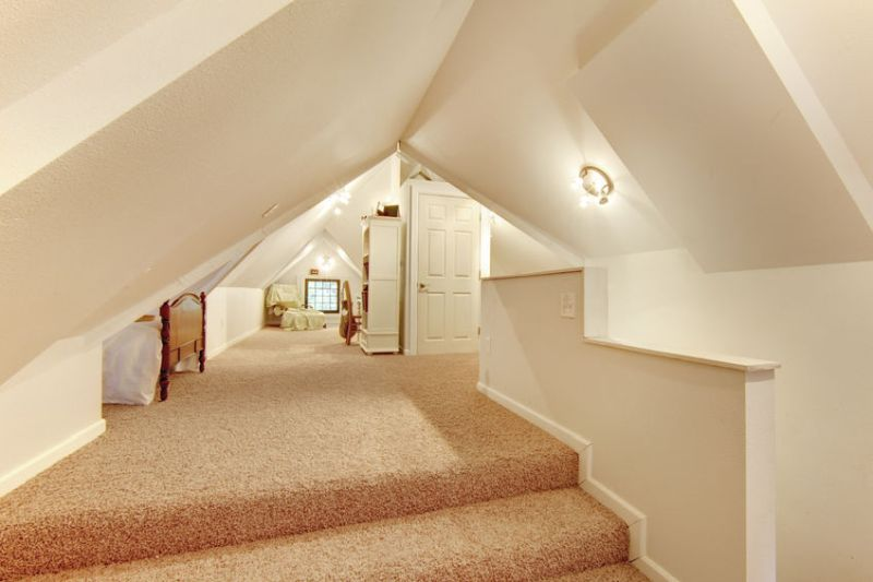 58329196 – lovely beige attic bedroom with vaulted ceiling and carpet floor.
