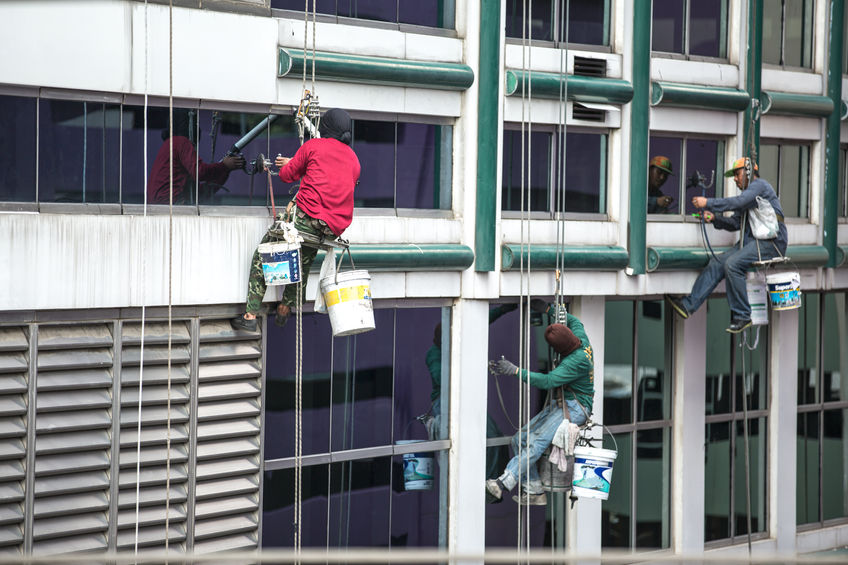 50623390 – group of workers cleaning windows service on high rise building