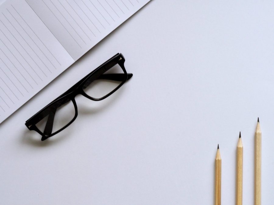 a desk with glasses, pencils and a notepad used in the examable article 'how not to study'.