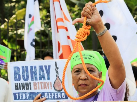 A woman holds up a noose during a protest against plans to reimpose the death penalty in the Philippines. Photo: CNS/Reuters