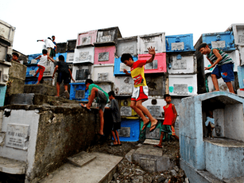 Children play on top of tombs in a cemetery in Philippine capital Manila ahead of All Souls' Day. (Photo: UCAN/Jhun Dantes)