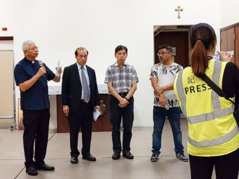 Father Peter Leung, left speaking to parishioners and the press on November 11.