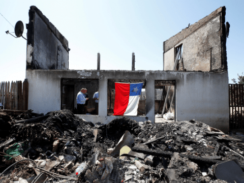 A Chilean flag is seen on a house in Valparaiso, Chile, Dec. 26, 2019, after it was destroyed by fire Christmas Eve. Valparaiso church workers estimated that at least 250 houses were destroyed on the hillsides, where the steep terrain made it difficult for firefighters to combat the blazes. (CNS photo/Rodrigo Garrido, Reuters)