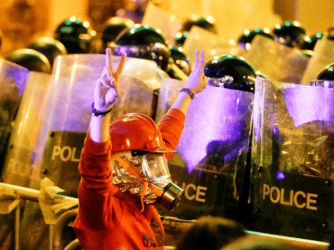 An anti-government protester in Beirut passing in front of riot police on December 15. Photo: CNS/Reuters