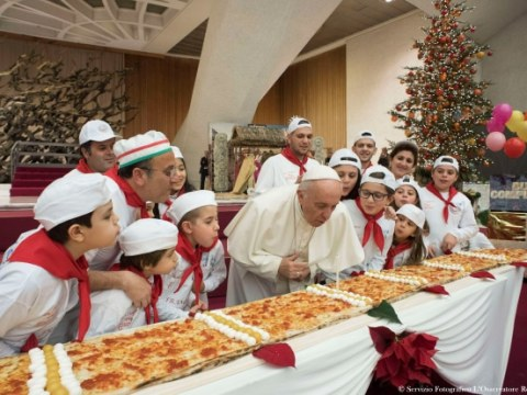Pope Francis blows out a candle on a four-metre-long pizza during on his 81st birthday on 17 December 2017 at the Vatican's Paul VI hall. Photo: CNS/L'Osservatore Romano