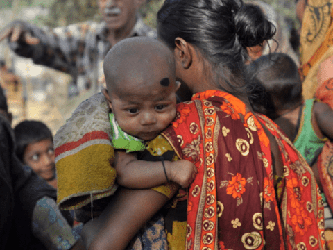 A mother carries her child during a village gathering in Habiganj district of Bangladesh. Photo: UCAN/Stephan Uttom