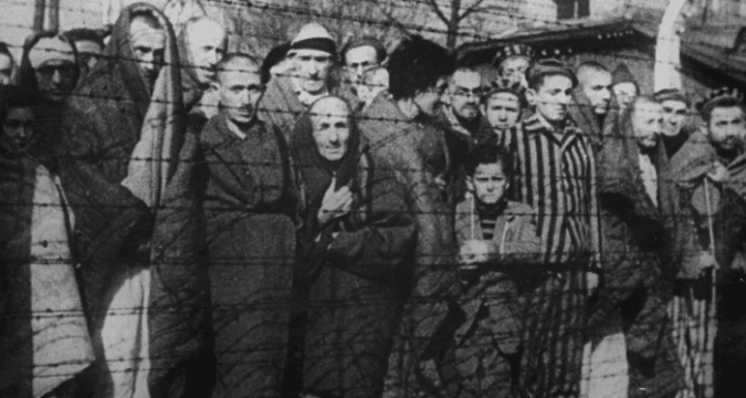 The haunted faces of men, women and children look on from behind barbed wire after the liberation of the Auschwitz-Birkenau death camp in 1945 in Oswiecim, Poland. File photo: CNS/Yad Vashem Archives via Reuters