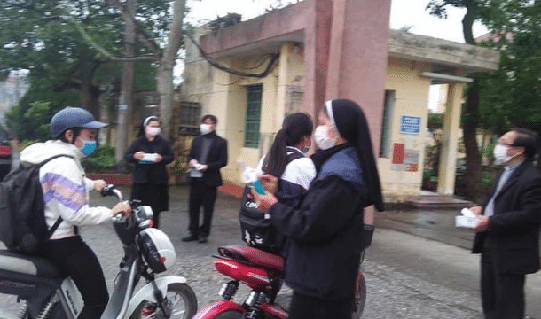 Priests and nuns offer medical masks to students in front of a high school in Vietnam's Thai Binh province on March 6. Photo: UCAN/ courtesy Nguyen Ngoc Nam Phong's Facebook page