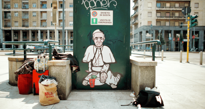 A mural depicting Pope Francis as a homeless man asking for charity seen in Milan on May 23. Photo: CNS/Reuters
