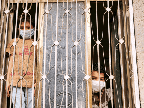 Children with facemasks look out the window of their home in Sanaa, Yemen, on June 7. Photo: CNS/Reuters
