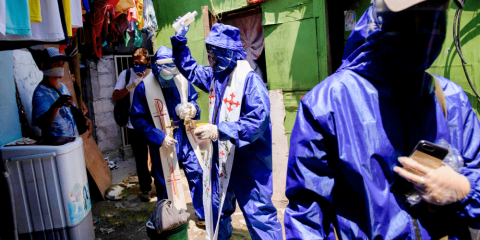 """Father Eduardo """"Ponpon"""" Vasquez Jr. uses holy water to bless shanty homes in a poor section of Manila, Philippines, on april 20 during the Covid-19 pandemic. Photo: CNS/Reuters"""