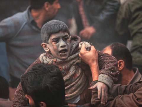 Men help a wounded boy who survived an airstrike by forces loyal to Bashar Assad in Damascus. File photo: CNS/Reuters
