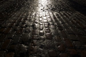 Wet cobblestones at night are dark and slippery.