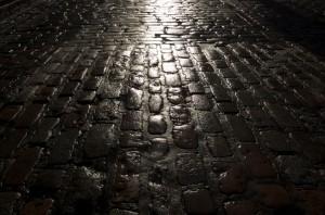 Wet cobblestones at night are dark and slippery.