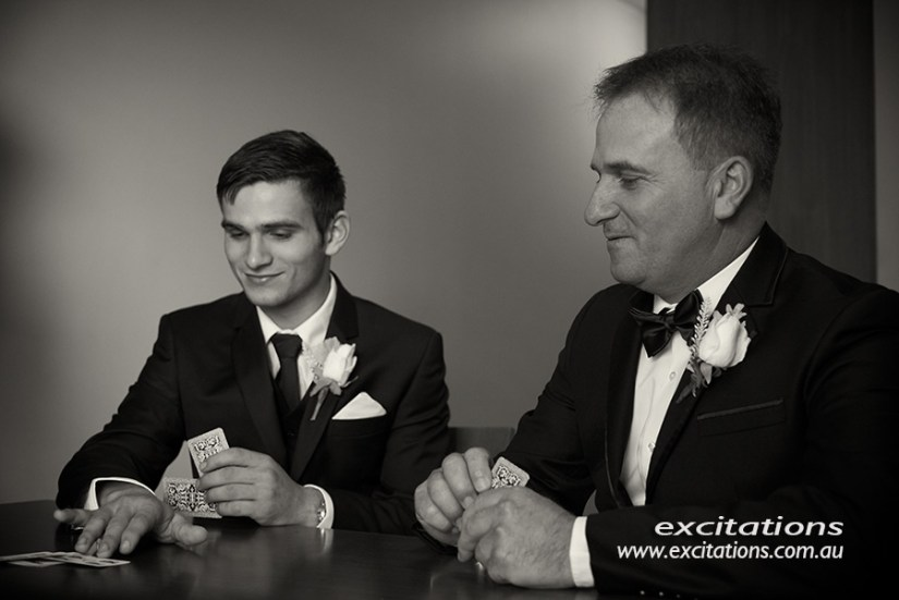 Black and white photo of groom and his father playing cards before his wedding. Photo by Excitations, photographers Mildura.
