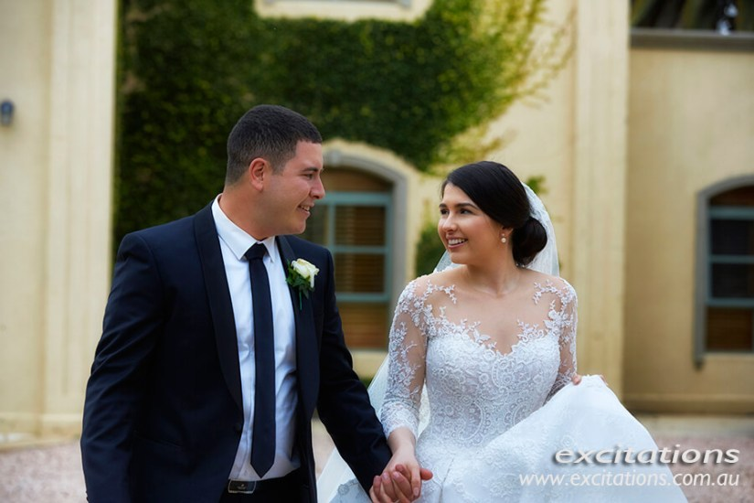 Bride and groom half length, walking and talking. Colour wedding photography by Excitations, Mildura photographers.