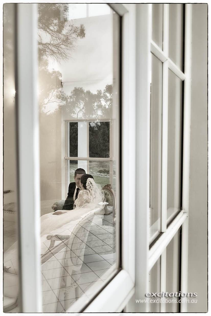 Bride and groom photographed through a window of a mansion. Wedding pictures by Excitations Mildura photographers.