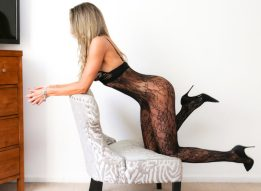 Esme posing on the chair in black body stocking.