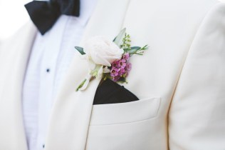 Boutonniere with white and purple flowers