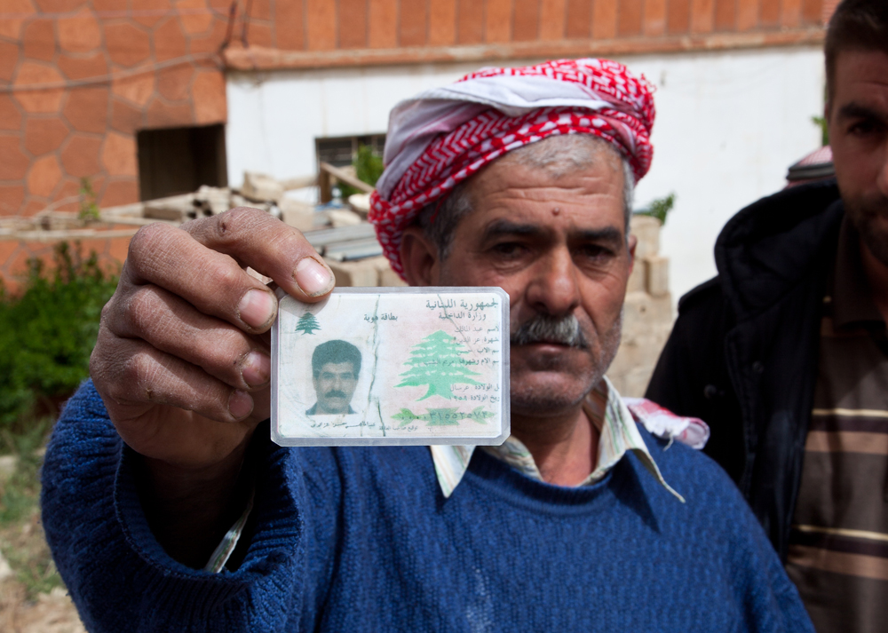 """What are we supposed to do, eat rocks?"" asks Ezzedine, 54, holding up his Lebanese ID card"