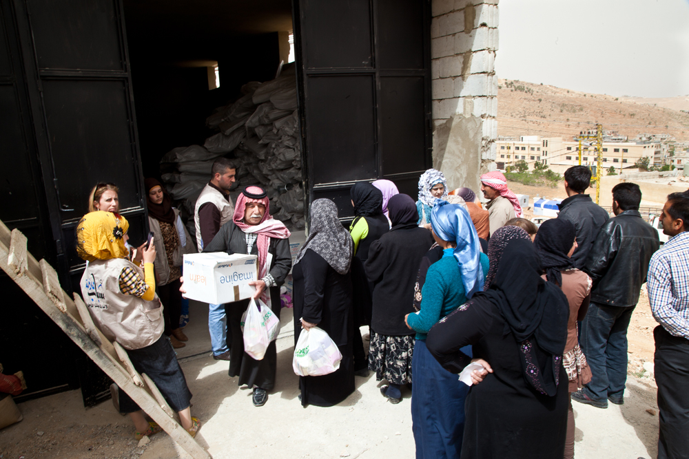 Lebanese returnees in the town of Arsal stand in line to receive food packages