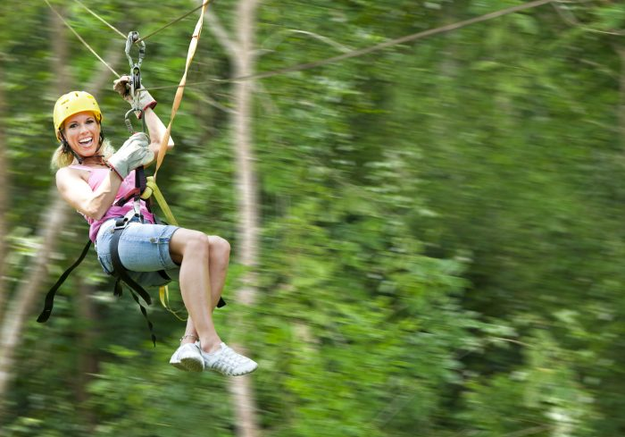 Confident woman flies through jungle on zipline canopy tour. Roatan, Honduras