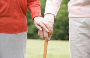 杖に手を添えあう老夫婦の手元