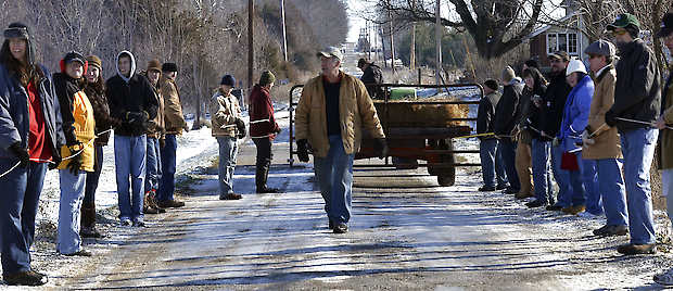 Alan Yegerlehner, center, reminds his volunteers to keep the lines taut as they prepare to move Yegerlehner's cattle to their winter pasture Saturday in rural Clay County near Clay City. Joseph C. Garza | Terre Haute Tribune-Star, Associated Press