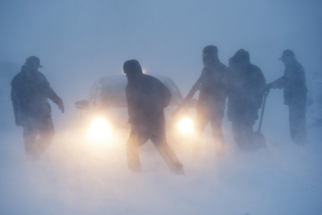 Several people attempt to free a vehicle from the snow in the Prairie Knights Casino & Resort parking lot during a blizzard on Sunday, Dec. 5, 2016. Severe winter conditions severely impacted the ability for Dakota Access Pipeline protesters to get to the Oceti Sakowin campground.