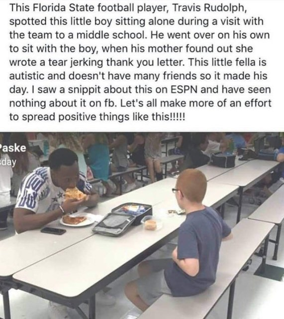 Travis Rudolph sitting with a child who's eating alone.