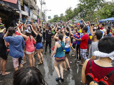 Thais and Westerners outside spraying each other with water during Thailand's New Year celebration, Songkran.