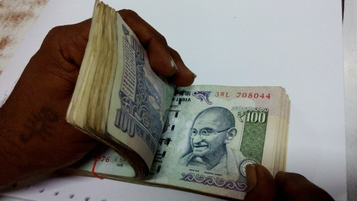 A person counting Indian Rupees wrapped in a rubber band.