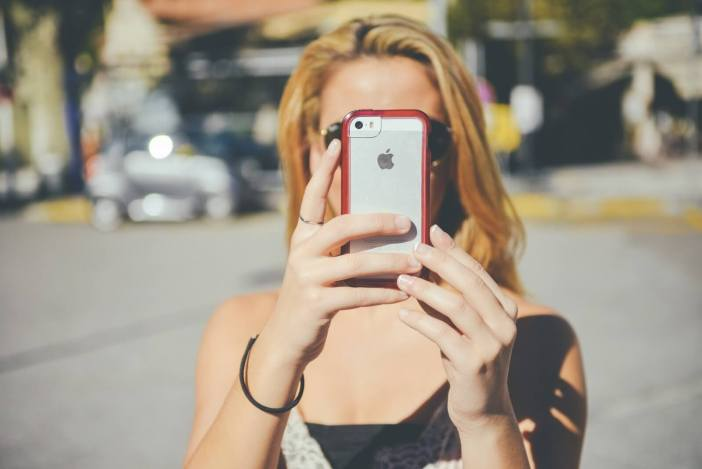 young-woman-photographing-self-on-sunny-day