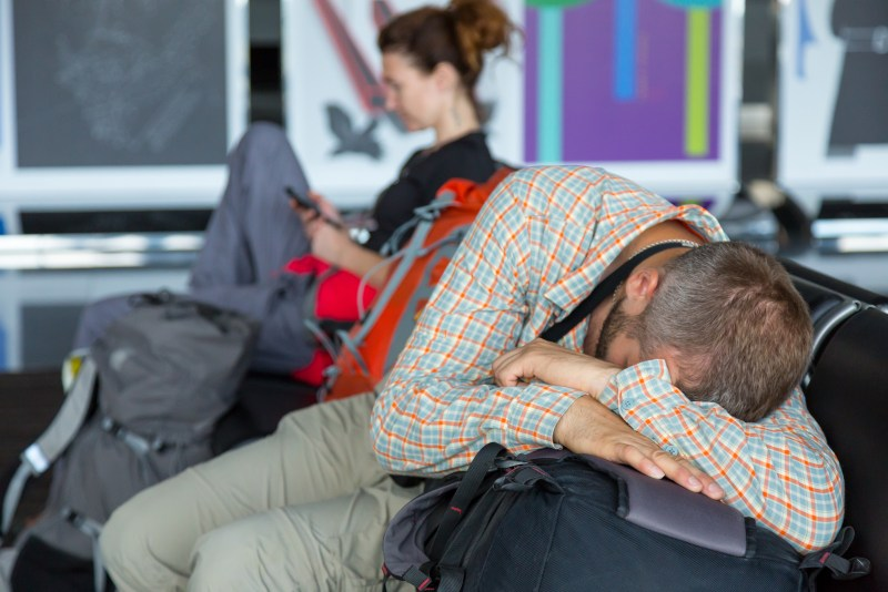 Passengers waiting for the air flight at airport terminal Man and woman sitting in chairs line sleeping browsing smart phone internet casual dress code heavy boots backpacks luggage building interior