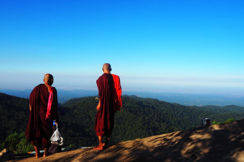 close up of back side of two Burmese monks at Kyaiktiyo pagoda with clear blue sky and green mountain background, Myanmar