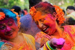 Ladies enjoying throwing coloured powder during Holi