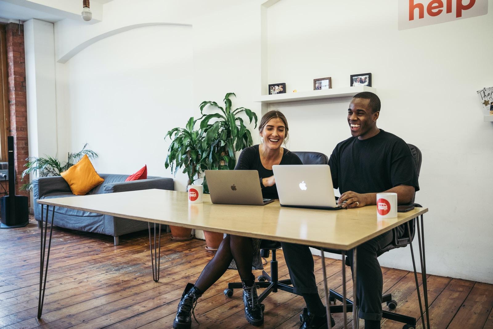 man in black long sleeve shirt sitting beside woman in black long sleeve shirt using macbook