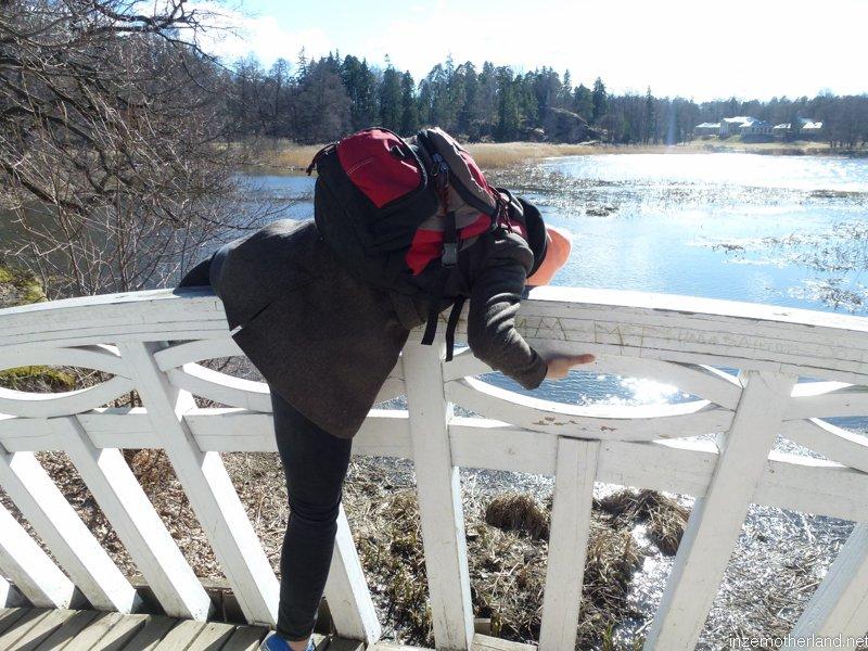 Nastya tries to climb onto the bridge.