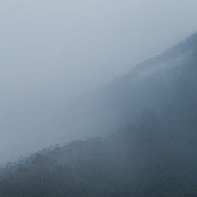 Rainy weather over the Sierra Nevada de Santa Marta mountain rainge, Colombia. This somewhat minimalistic image gives a strong impression of remote and hostile wilderness, only showing mysterious outlines of the mountains, and palm tree forest growing on the ridges.