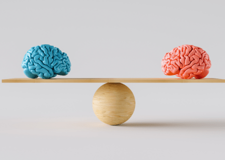 An image of two brains on a scale to represent cognitive biases.