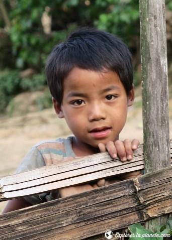 Enfant Akha sur le bord d'une cloture au Laos