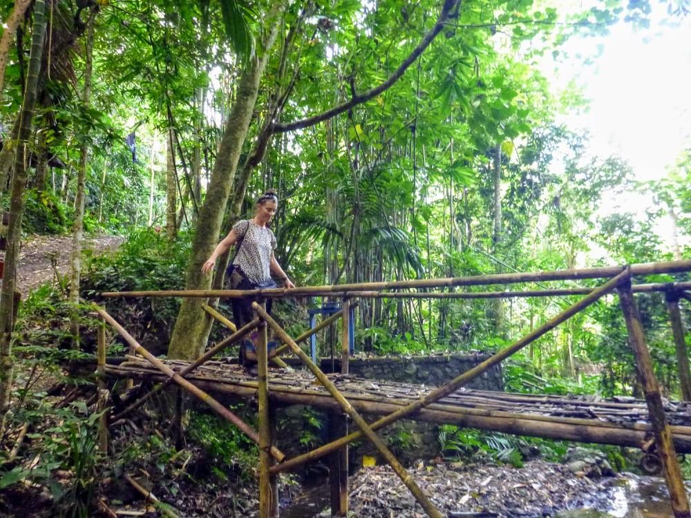 AdventureGirl Andrea Crossing Old hand made bridge in Bali Indonesia