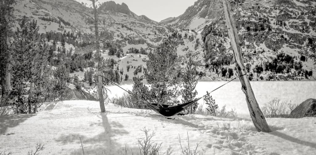 Camping hammock near a lake by the mountains