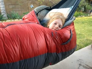 children camping in parachute nylon hammocks