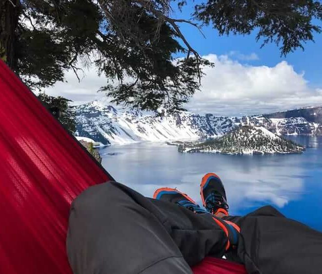 sitting in a portable ultralight serac sequoia camping hammock with a view of crater lake national park